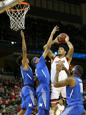Cincinnati Bearcats guard Jarron Cumberland (34) takes on three Memphis Tigers defenders to the basket in the first half during the college basketball game between the Memphis Tigers and the Cincinnati Bearcats, Sunday, Dec. 31, 2017, at BB&T Arena in Cincinnati.