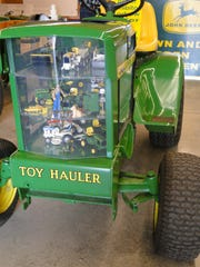A John Deere 1974 Model 112 showcase tractor (toys inside engine compartment)