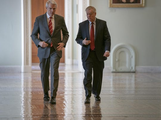 Sen. Rob Portman, R-Ohio, left, and Senate Judiciary Committee Chairman Lindsey Graham, R-S.C., walk to a meeting as an 11th-hour Republican rescue mission to keep President Donald Trump from a Senate defeat on his signature issue of building barriers along the southwest border seems near collapse, at the Capitol in Washington, Wednesday, March 13, 2019.