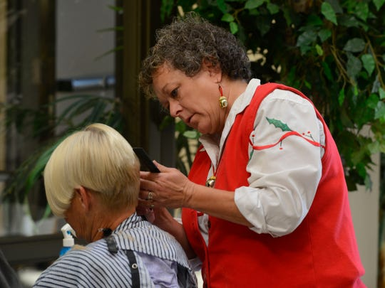 Valorie Maldonado of Cuts By Us, finishes up a free haircut Saturday during the Christmas Dinner for the Homeless at First Baptist Church. Free haircuts, a dinner, toys for children, blankets and coats were all included.