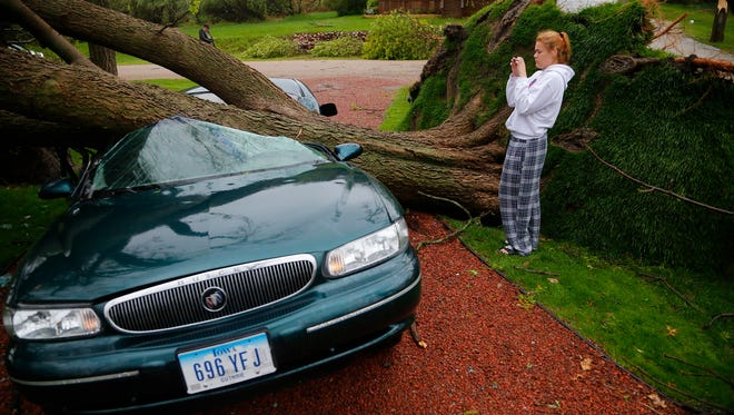 Emilia Merritt, 18, looks at the damage to her car after a tree fell during a storm at her home on Panorama Dr. in Lake Panorama, Iowa, Monday, May 12, 2014.  At least eight condos in the Boulder Cover Condo Association were heavily damaged after a storm ripped through two sections of Lake Panorama, Sunday, May 11, 2014. The National Weather Service plans to send a survey team to the area to determine whether the damage was caused by a tornado.  (AP Photo/The Des Moines Register, Zach Boyden-Holmes)