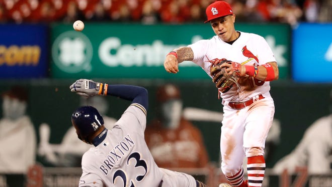 Milwaukee Brewers' Keon Broxton (23) is out as St. Louis Cardinals second baseman Kolten Wong turns the double play during the seventh inning of a baseball game Thursday, May 4, 2017, in St. Louis. The Brewers' Orlando Arcia was out at first.