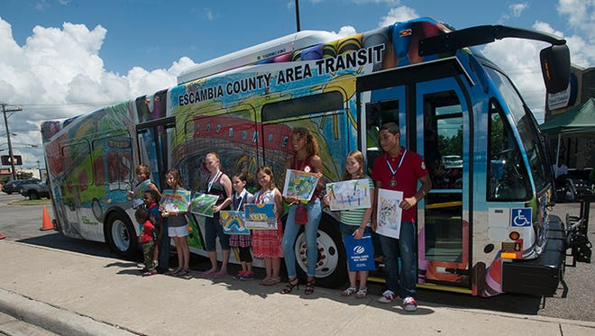 Winners of the Escambia County Area Transit Youth Art Contest pose for photos in 2015 next to a bus featuring some of the art created by the students.