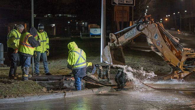 A Livonia DPW Public Service crew repairs a water main break at the corner of Stark Road and the eastbound Schoolcraft/Jeffries service drive, one of two water main breaks along the freeway service drive. The city declared a boil water alert due to low water pressure. Eastbound I-96 Jeffries freeway was briefly closed because of water on the pavement.