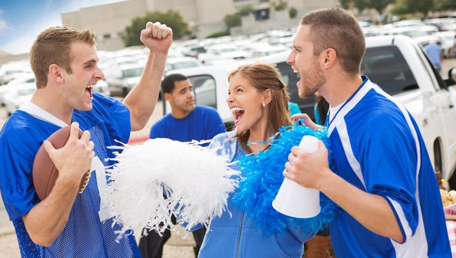 Excited football fans at a stadium tailgate party.