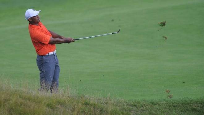 Tiger Woods chips onto the 18th green during a practice round for the PGA Championship at Whistling Straits on Tuesday.