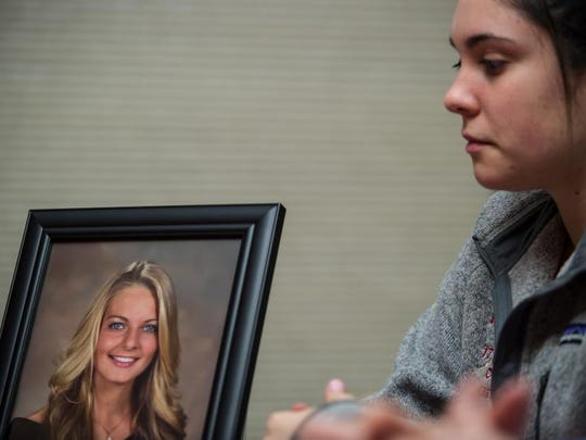 With a portrait of friend Nicole Trott in the background, friend Katie Hungrige participates in a meeting of Nicole's Heart Foundation in Old Bridge.