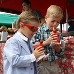 Brothers Jonah, 5, left, and Robby Holtzmann, 7, sip freshly made strawberry smoothies during the 37th Annual Strawberry Festival at St. John the Baptist Catholic Church in Starlight on Saturday.