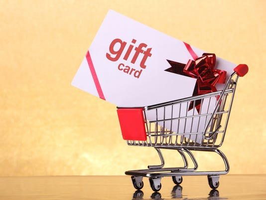 A large gift card in a shopping cart on a peach background