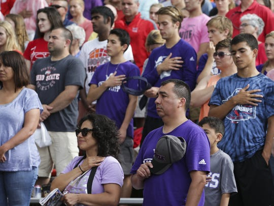 People in the crowd pay their respects with a moment of silence just before the National Anthem for West Lafayette High School student Christian Burns, who passed away on May 3 in a car accident.