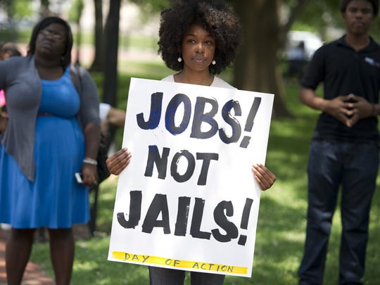 """A demonstrator holds a sign during a rally following a protest march to end the so-called """"war on drugs,"""" which they say leads to mass incarceration of African Americans."""