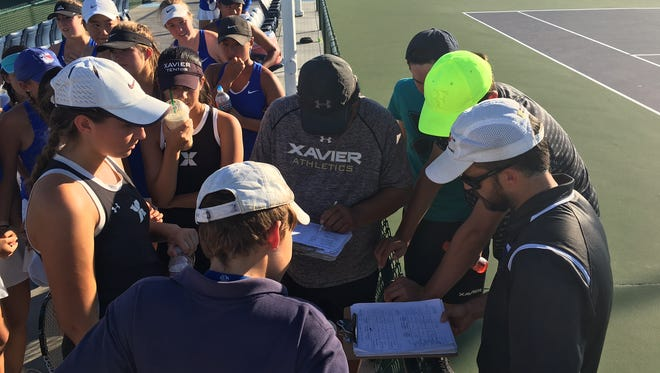 Xavier tennis coach Tony Jadulang (center) and Cate High coach Trevor Thorpe (right) add up the total games while both teams look on anxiously Friday at the Indian Wells Tennis Garden.