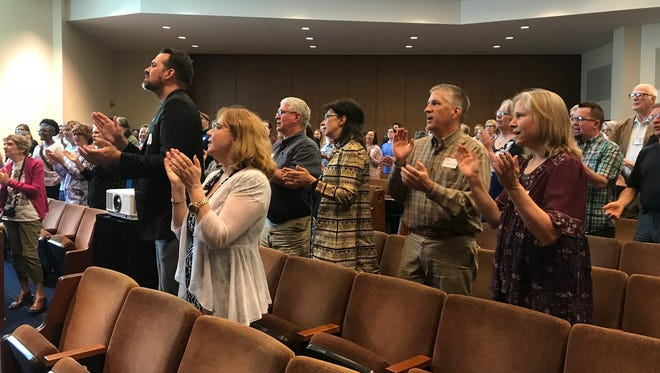 Attendees sing during a public theology and activism course at The Temple on Friday afternoon. The event was hosted by local faith groups and put on by the Repairers of the Breach nonprofit.