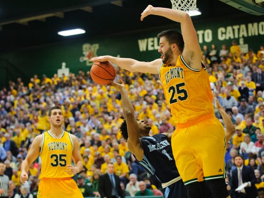 Vermont's Drew urquhart (25) blocks the shot by Maine's