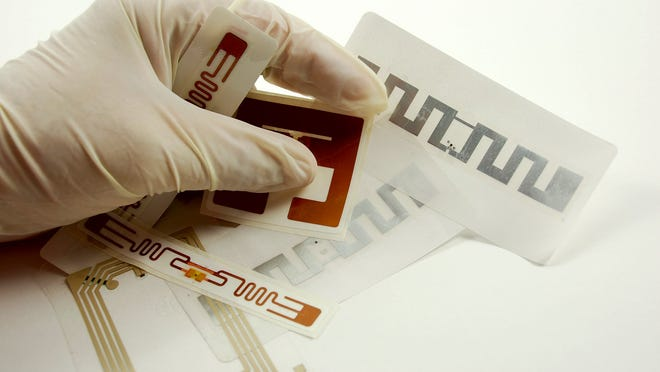 A hand, wearing a medical glove, holds several RFID tags.