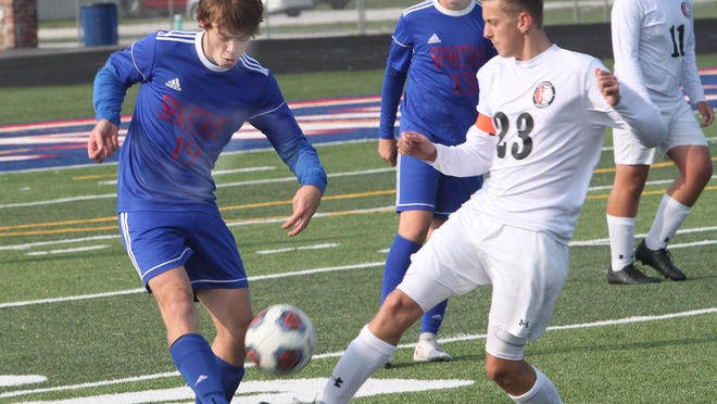 Moberly defender Landon Stone (left) clears the soccer ball before Kirksville's Bryce Ensign arrives to try and garner possession Saturday morning during each school's second round-robin game of the Spartans Soccer Invitational held at Dr. Lary K. Noel Spartan Stadium. Moberly won the game 1-0.