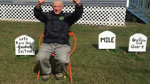 Brent Maynard of York Beach, Maine, president of the York Metric Association, poses with tombstones as he calls for Americans to move from the English system of measurement to the metric system.