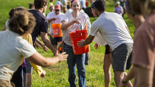 Gwen Roberts of Essex with Team Liquid Squirrel carries a bucket of water that everyone in line has to touch during the bucket brigade challenge during the first Farmer Olympics on Wednesday at Maple Wind Farm in Bolton.