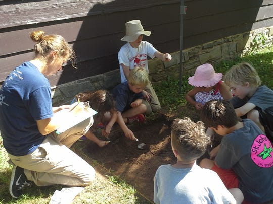 Monmouth University student Megan Kleeschulte (left) gives campers a hands-on lesson in archaeology.