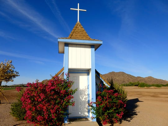 The small roadside chapel sits at the edge of farm fields along U.S. 95 about 14 miles north of Yuma.