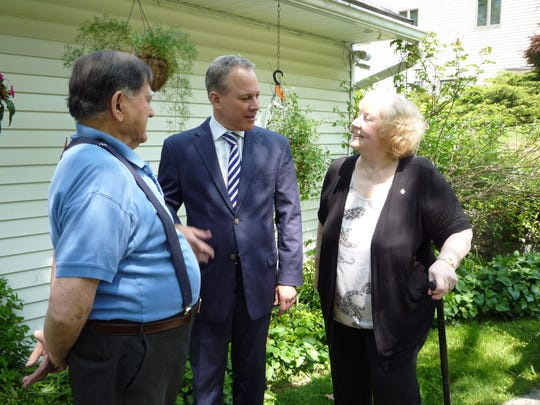 State Attorney General Eric Schneiderman, center, meets with Miguel Ortiz, left and Carole Ortiz, who were able to avoid foreclosure thanks to the Mortgage Assistance Program.