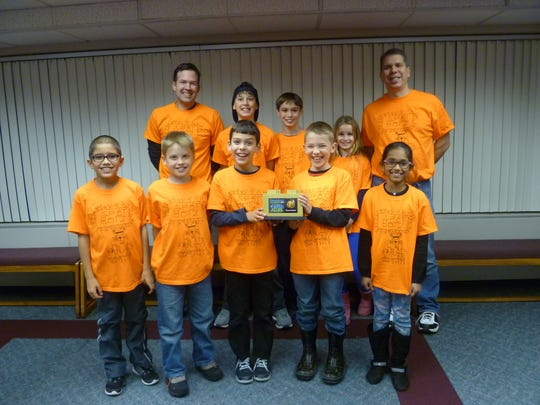 The Spot Botz team poses with its first-place presentation award from the regional competition in November. Front row, left to right, Braeden Shea, Justin Del Pup, Ben Fleming, Conner Duffy, Nityasri Kasula. Back row, left to right, Coach Chris Duffy, Lochlain Hart, Asher Hart, Jacqueline Brown and Coach Joe Fleming.