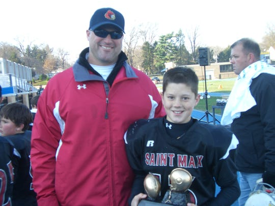 Alex and his dad pose for a picture during the sixth grade CYO Championship Game when Alex played for St. Maximilian Kolbe in West Chester, Pa.