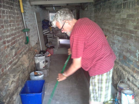 """Bobby Yowell sweeps the storage area beneath the porch when he lived at 301 W. Beverley St. in Staunton. """"Bobby and his broom,"""" says friend and former neighbor Steve Brotzman. Brotzman says Bobby used to go downtown and sweep the sidewalks."""