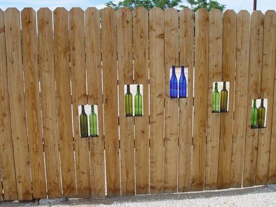 A simple board fence is transformed by bottle windows