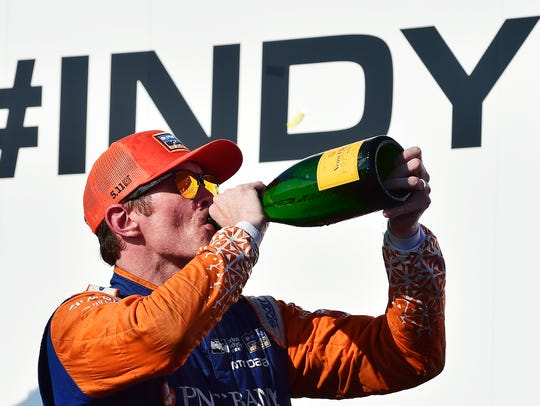 Scott Dixon celebrates after winning an IndyCar auto