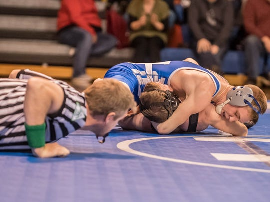 Harper Creek's Ethan Bishop goes for the pin against Marshall at 125 pounds on Wednesday.