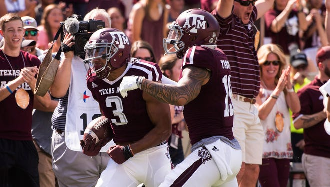 Texas A&M Aggies wide receiver Christian Kirk (3) and wide receiver Jeremy Tabuyo (19) celebrate a touchdown against the Tennessee Volunteers during the first quarter at Kyle Field.