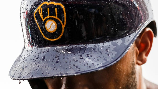 Eric Thames of the Brewers walks into the dugout during a rain delay in the sixth inning on Sunday in Cincinnati.