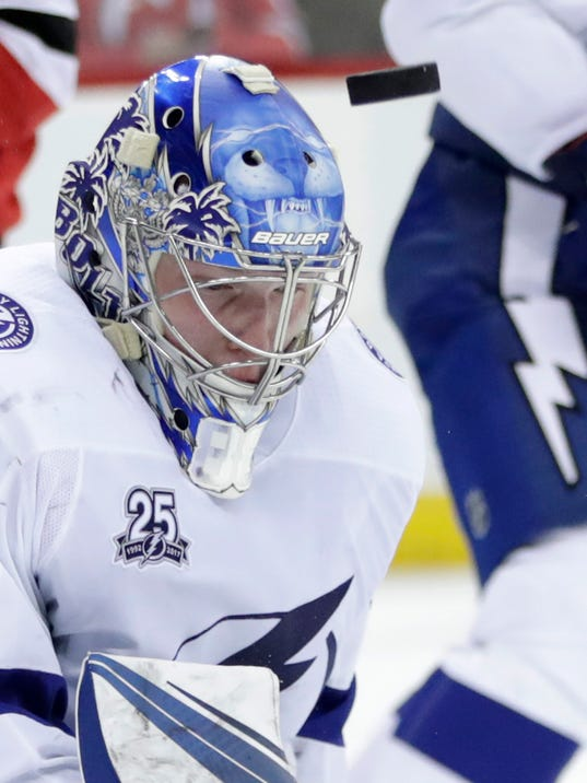 The puck kicks up as Tampa Bay Lightning goaltender Andrei Vasilevskiy (88), of Russia, blocks a shot from the New Jersey Devils during the second period of an NHL hockey game, Saturday, March 24, 2018, in Newark, N.J. (AP Photo/Julio Cortez)