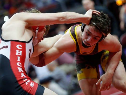 New Hampton's Noah Glaser (left) wrestles with PCM's
