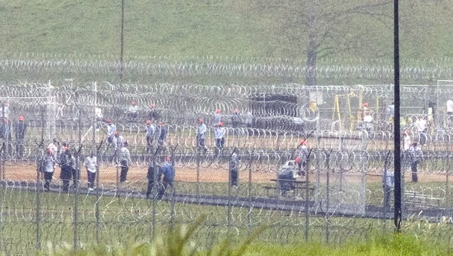 File photo of inmates viewed through the security fences at the Augusta Correctional Center in Craigsville on May 11, 2006.