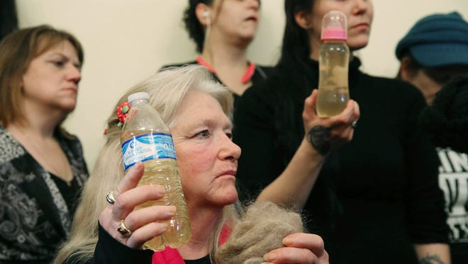 Flint, Michigan resident Gladyes Williamson, left, holds a bottle of the city's water and a clump of her hair at a news conference following a U.S. House Oversight and Government Reform Committee hearing on the city's water crisis in February.