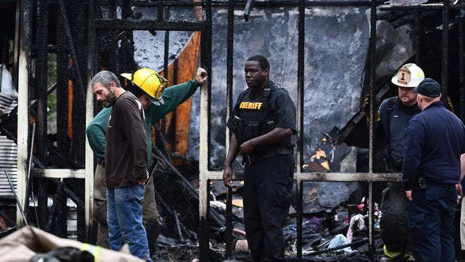 The boyfriend, left, of a women who died in an early morning house fire stands near Anderson County firemen and a sheriff's deputy working at the scene at 909 Shirley Store Road in Anderson on Tuesday.