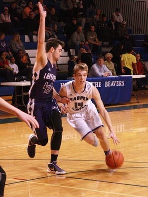 Harper Creek's Sophomore, Jon Taylor dribbles past Lakeview defender, Senior, Nick Adams during Tuesday night's game