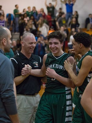Marc Spinelli (center) celebrates with coaches and teamates after Yorktown beat Spring Valley during the Class AA Boys High School Basketball Quarterfinal on Friday, Feb. 24 at Spring Valley High School.