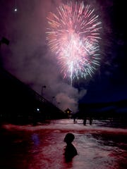 Spectators watch the annual Fourth of July fireworks at the Naples Pier on July 4, 2014.