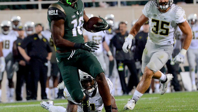 Spartan Aaron Burbridge (16) looks to the endzone as he gets past an Oregon on his way to score in the second quarter at Spartan Stadium Saturday, September 12, 2015 in East Lansing, Michigan. The touchdown gave the Spartans a 14-7 lead.