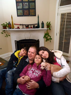 David Bundy is photographed on Sunday, Feb. 23, 2014, with three of four children he and his wife, Lisa, recently adopted from Ukraine. From left are Max, Alla and Karina. Lisa Bundy remained in Ukraine until the adoption of their daughter Nastia could be finalized.