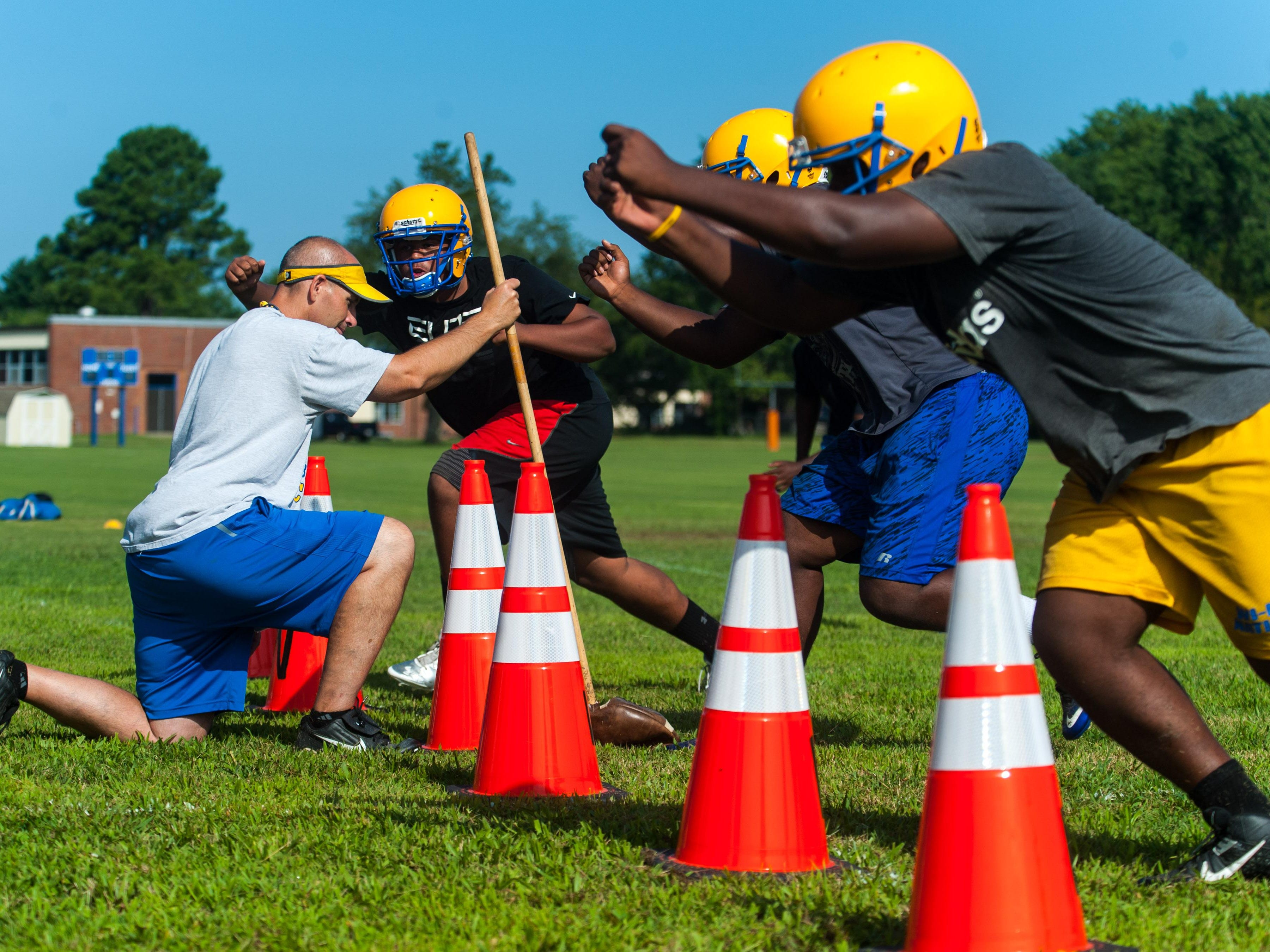 Wicomico High head coach Patrick McGlinchey works with linemen on the second day of practice.