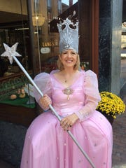 """Katie Spurlock, owner of H.L. Lang and Co. Jewelers, is Glenda """"the good witch"""" from the Wizard of Oz for Staunton's Trick-or-Treat Downtown on Saturday, Oct. 29, 2016, in Staunton, Va. She said she ran out of candy, so she had to start handing out """"the good stuff,"""" aka Ferrero Rochers that she and her staff usually eat."""