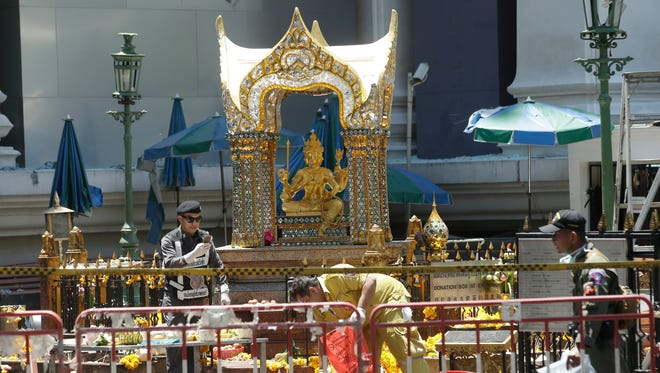 Police and officials work near the statue of Phra Phrom, the Thai interpretation of the Hindu god Brahma, at the Erawan Shrine at Rajprasong intersection the day after an explosion in Bangkok, Thailand, Tuesday, Aug. 18, . Thailand's prime minister on Tuesday promised that authorities would quickly track down those responsible for the central Bangkok bombing which he described as the country's worst attack ever.