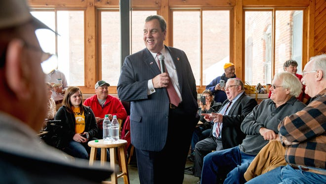 Chris Christie smiles as he jokes with visitors to Elly's Tea and Coffee House in Muscatine, Iowa, on Dec. 29, 2015.