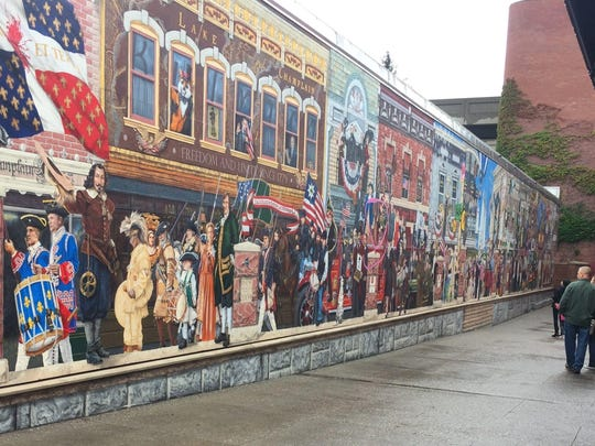 """A pedestrian glances at the """"Everybody Loves a Parade"""" mural in Leahy way in downtown Burlington on Monday, Oct. 9, 2017."""