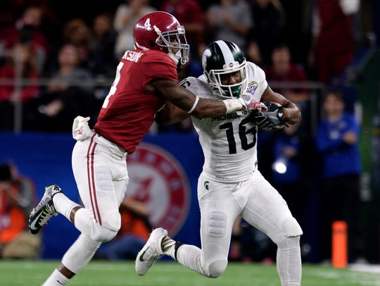 Spartan receiver Aaron Burbridge (16) stiff arms Alabama's