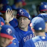 Texas starter Derek Holland greets teammates after finishing his two innings Thursday.